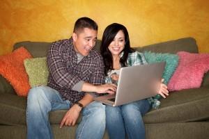 Hispanic couple editing website on computer